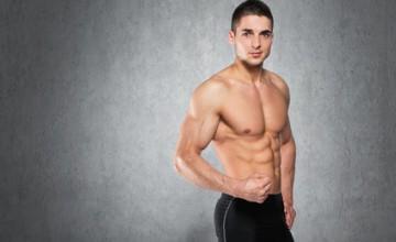 Bodybuilder vor grauer Wand