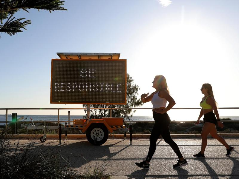 Walking in Corona-Zeiten: Frauen gehen in Perth an einer digitalen Anzeige mit der Aufschrift «Be Responsible» (Seid verantwortungsvoll) vorbei. Foto: Richard Wainwright/AAP/dpa                                 Richard Wainwright